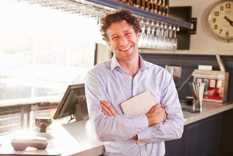 Manlig restaurangägare som rymmer den digitala minnestavlan, stående arkivbilder
