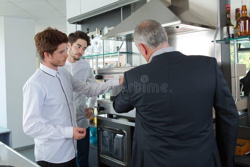 Manlig restaurangchef som övervakar arbetare arkivfoto