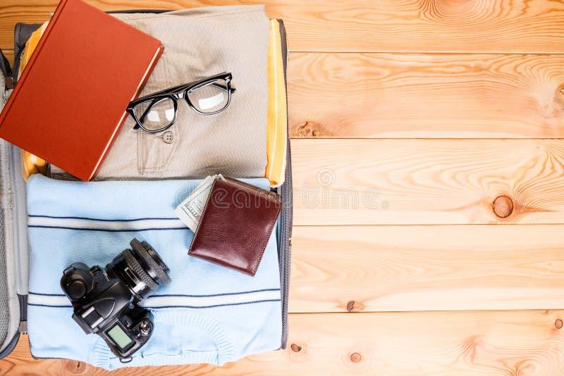 Manlig resväska med kläder och tillbehör på träbräden, brunnsort royaltyfria bilder