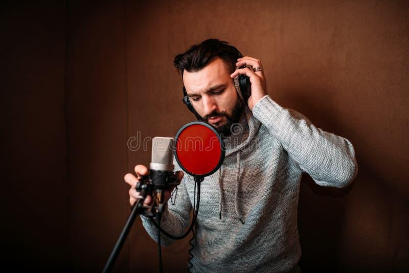 Manlig sångare som antecknar en sång i musikstudio arkivbild