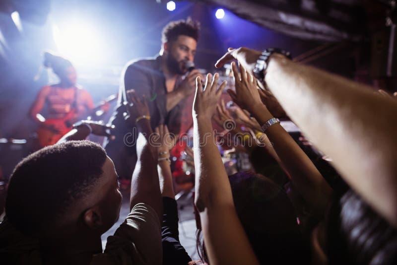 Manlig sångare som utför under folkmassan på nattklubben royaltyfria bilder