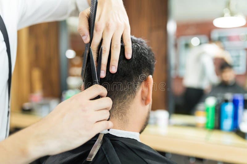 Manlig sakkunnig ` s räcker genom att använda sax till klippt hår för klient` s royaltyfri foto
