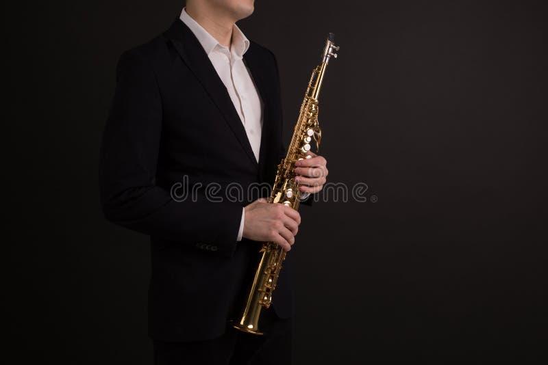 Manlig saxofonist i den svarta klassiska dräkten som rymmer en sopransaxofon som står på en svart bakgrundssidosikt royaltyfria bilder