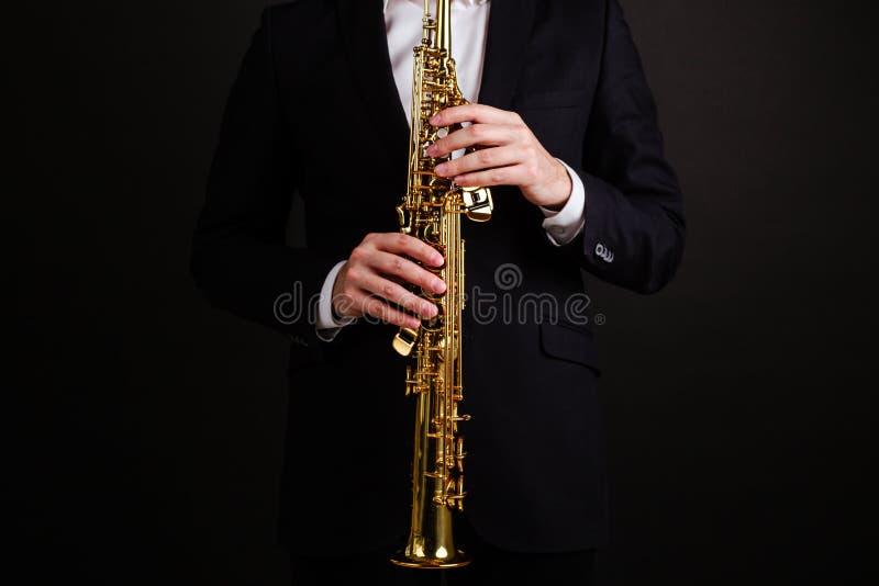 Manlig saxofonist i en svart klassisk dräkt som spelar på sopransaxofonen, medan stå på en svart bakgrund arkivbild