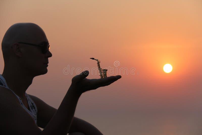 Manlig saxofonist på solnedgången Alt- saxofon på solnedgången silhouette royaltyfria bilder
