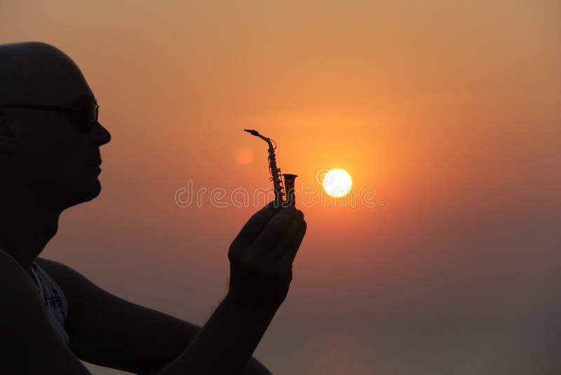 Manlig saxofonist på solnedgången Alt- saxofon på solnedgången silhouette arkivbilder