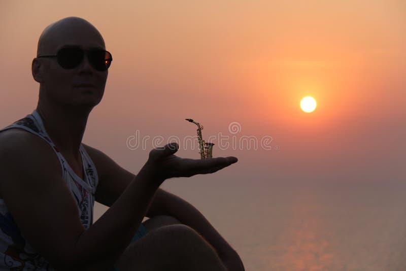 Manlig saxofonist på solnedgången Alt- saxofon på solnedgången silhouette fotografering för bildbyråer