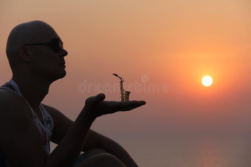 Manlig saxofonist på solnedgången Alt- saxofon på solnedgången silhouette royaltyfri foto