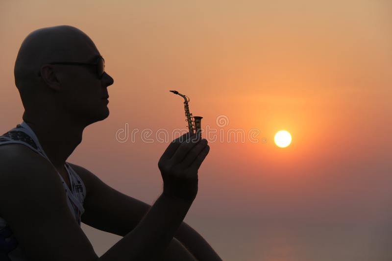 Manlig saxofonist på solnedgången Alt- saxofon på solnedgången silhouette arkivfoto