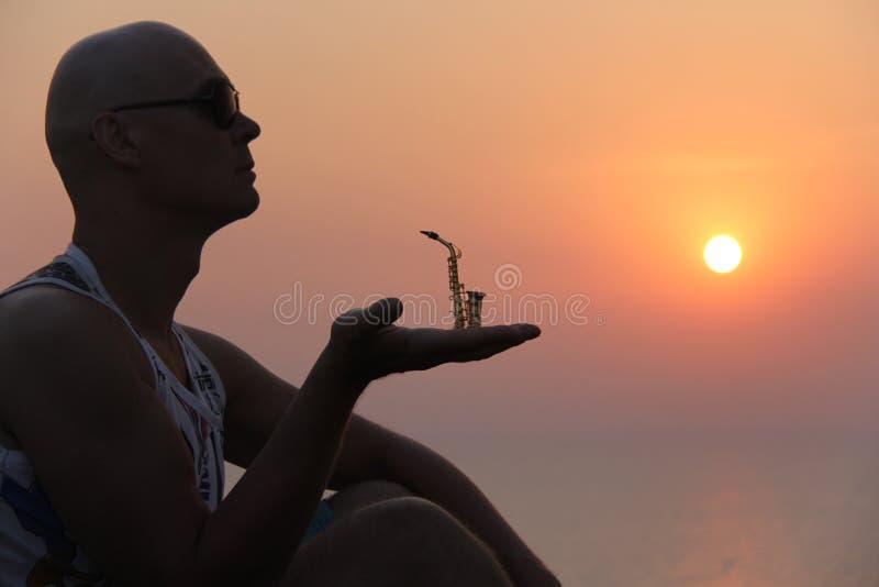 Manlig saxofonist på solnedgången Alt- saxofon på solnedgången silhouette arkivbild