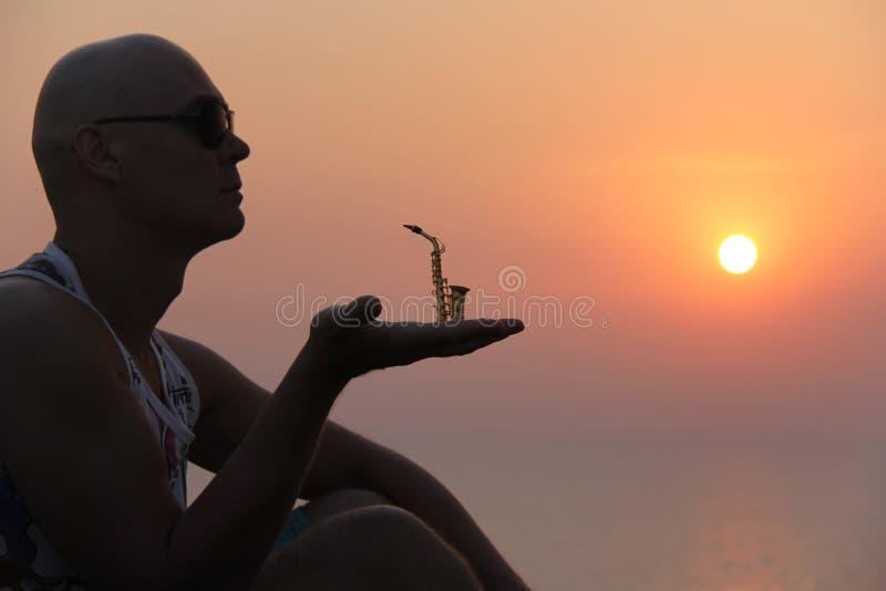 Manlig saxofonist på solnedgången Alt- saxofon på solnedgången silhouette arkivfoton
