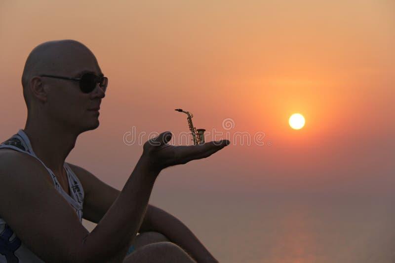 Manlig saxofonist på solnedgången Alt- saxofon på solnedgången silhouette royaltyfria foton