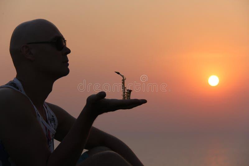 Manlig saxofonist på solnedgången Alt- saxofon på solnedgången silhouette royaltyfri fotografi