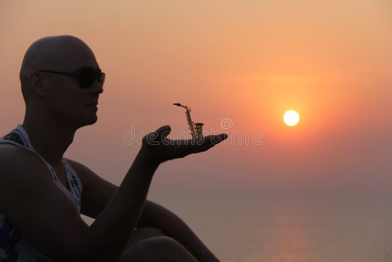 Manlig saxofonist på solnedgången Alt- saxofon på solnedgången silhouette royaltyfri bild