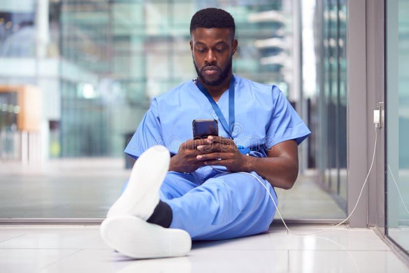 Manlig sjukvårdspersonal på sjukhus som är beroende av att använda mobiltelefon på arbetet royaltyfria foton