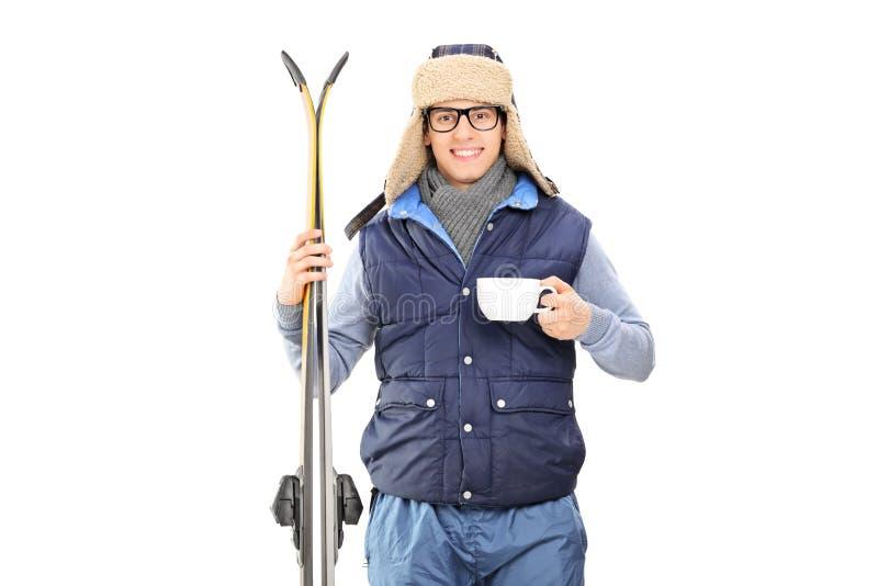 Manlig skidåkare som rymmer en kopp av varmt te royaltyfri bild