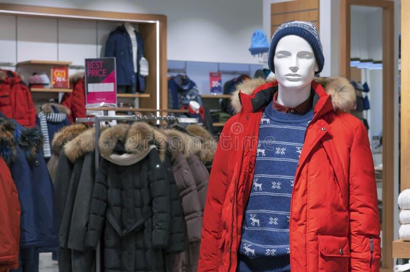 Manlig skyltdocka i ett rött omslag för vinter och en stucken hatt arkivbild