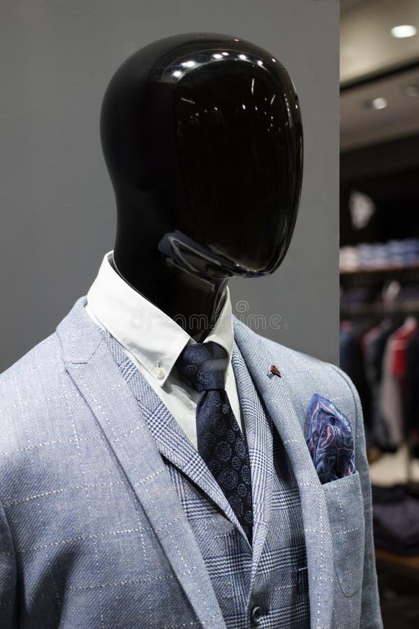 Manlig skyltdocka som bär ett omslag och ett band i ett boutiquefönster arkivbilder