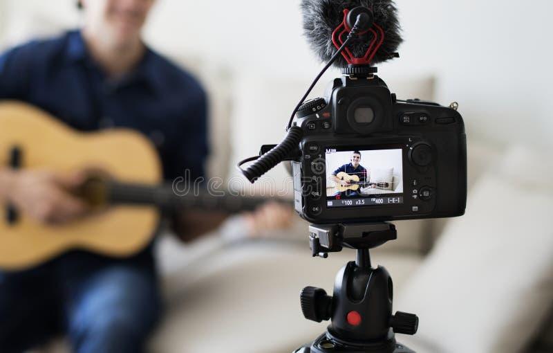 Manlig släkt TV-sändning för bloggerinspelning musik hemma arkivbild