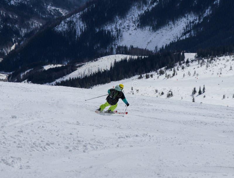 Manlig sluttande skidåkareskidåkning Pojken som stiger ned ner på, skidar Snida positionen Atletic diagram Gul hjälm Svart ryggsä royaltyfria bilder