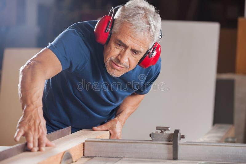 Manlig snickare Cutting Wood With Tablesaw fotografering för bildbyråer