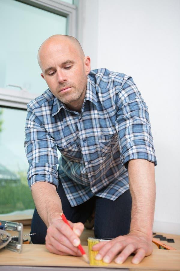 Manlig snickare som arbetar med träblyertspennan arkivbilder
