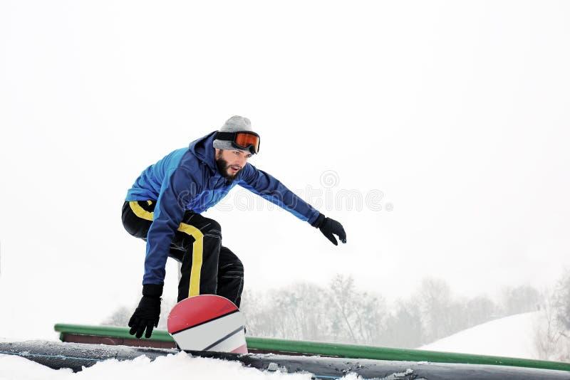 Manlig snowboarder som gör trick på vintersemesterorten royaltyfri foto