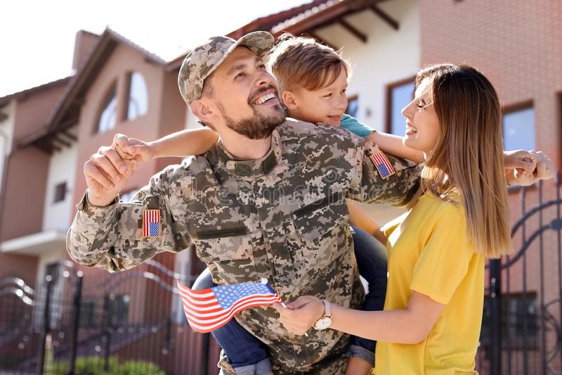 Manlig soldat som utomhus återförenas med hans familj Militärtjänst arkivbild