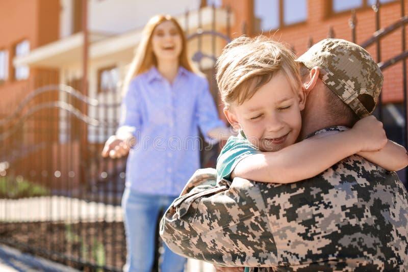 Manlig soldat som utomhus återförenas med hans familj Militärtjänst royaltyfria foton