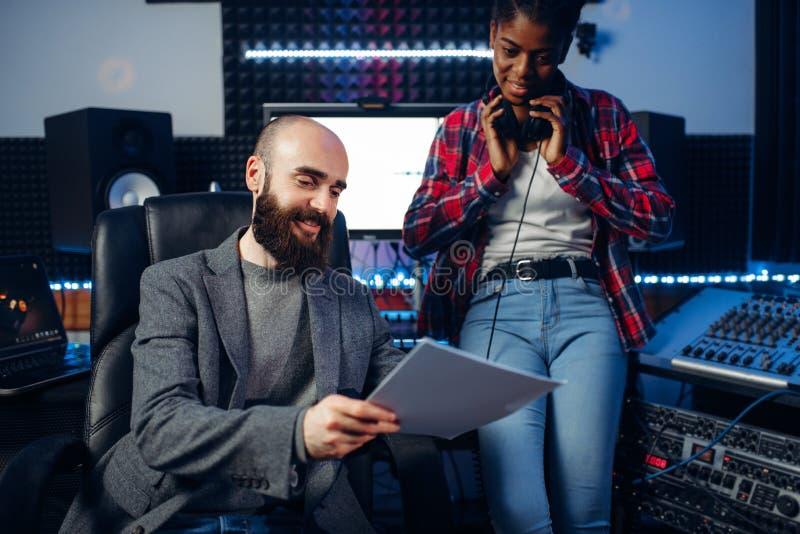 Manlig solid producent och kvinnlig sångare i studio arkivfoto