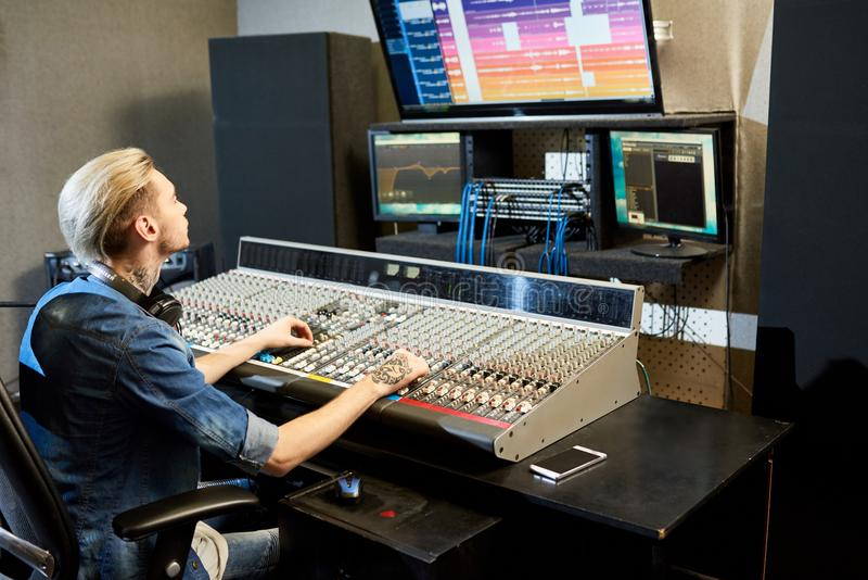 Manlig solid tekniker som redigerar filmmusik royaltyfri bild
