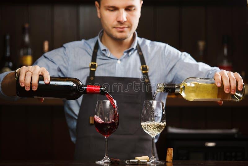 Manlig sommelier som häller rött och vitt vin in i lång-stemmed vinglas royaltyfri foto