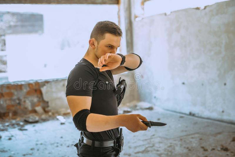 Manlig special solider med kamouflage att göra en självförsvarövning med kniven arkivbild