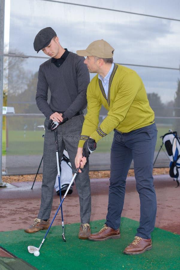 Manlig spelare för golf för golfinstruktörundervisning royaltyfria bilder