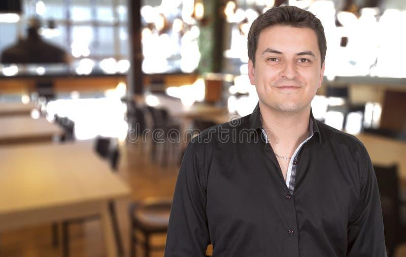 Manlig stående av att le stolt ägaremananseende på hans restaurang royaltyfria foton