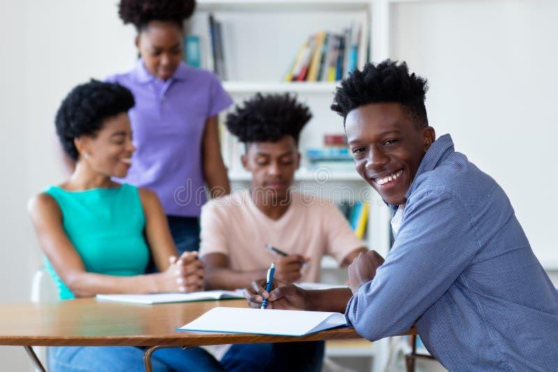 Manlig student för afrikansk amerikan som lär på skrivbordet på skola royaltyfria foton