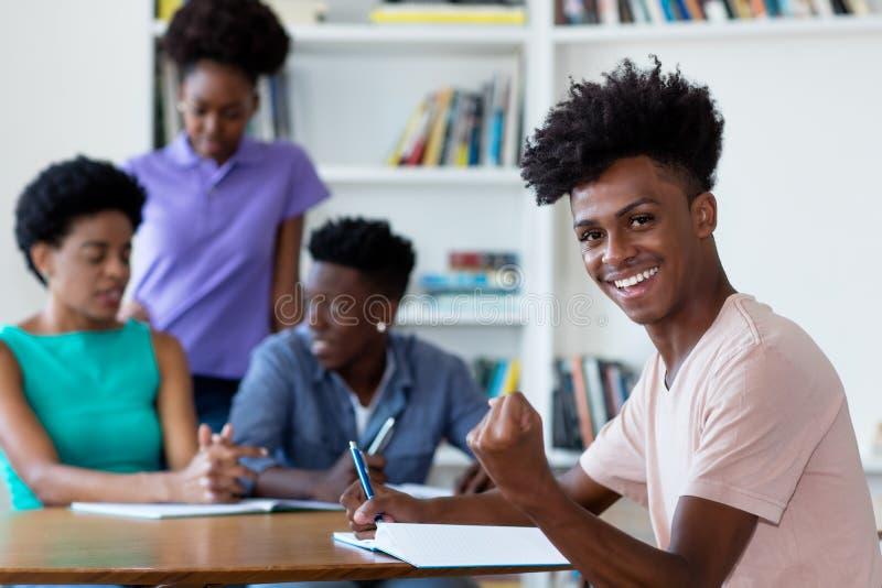 Manlig student för lyckad afrikansk amerikan som lär på skrivbordet på skola arkivbilder