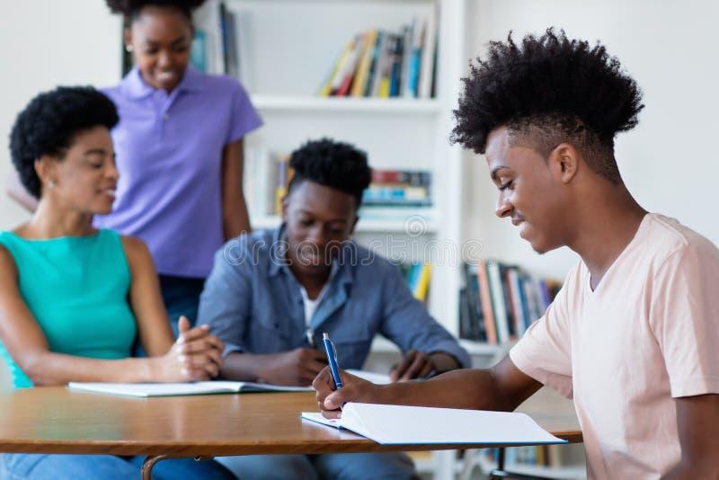 Manlig student för smart afrikansk amerikan som lär på skrivbordet på skola royaltyfria foton