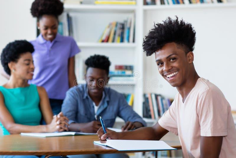 Manlig student för ung afrikansk amerikan som lär på skrivbordet på skola arkivfoton