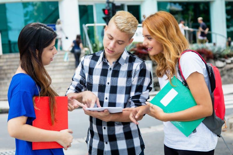Manlig student i diskussion med caucasian kvinnliga studenter royaltyfri bild