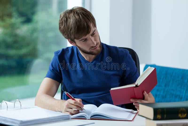 Manlig student som lär för examen arkivbild