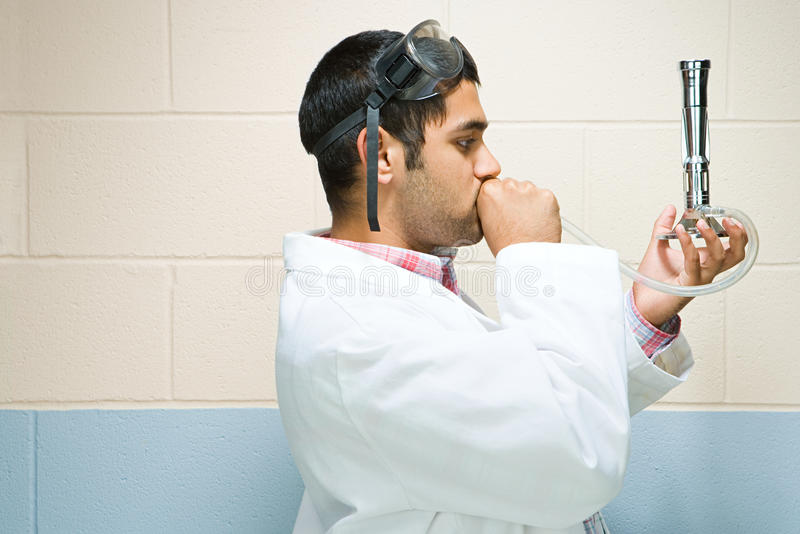 Manlig student som utför ett experiment royaltyfri foto