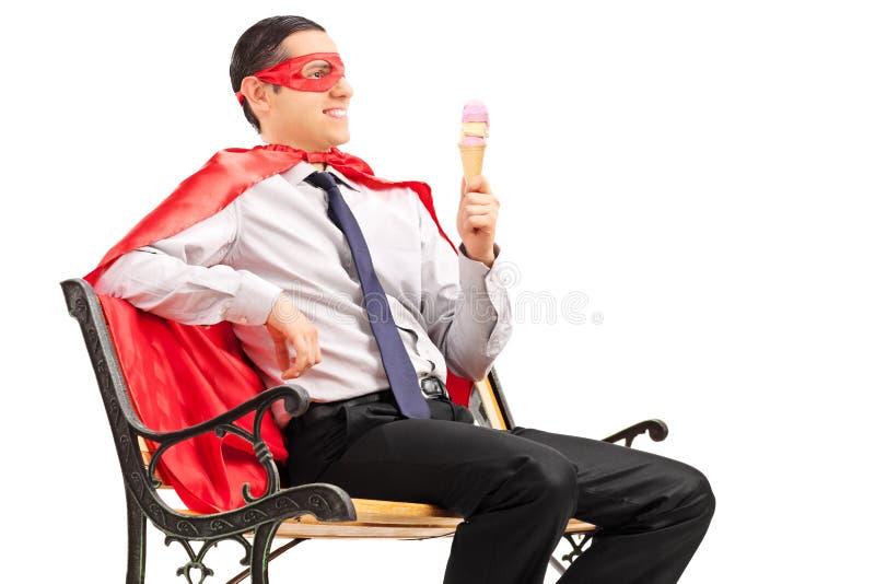 Manlig superhero som äter en glass som placeras på en bänk royaltyfria foton