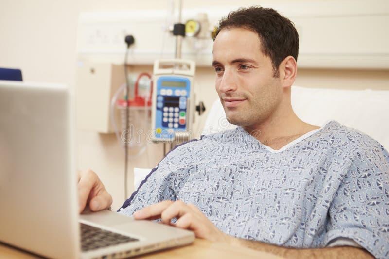 Manlig tålmodig användande bärbar dator i sjukhussäng arkivfoto