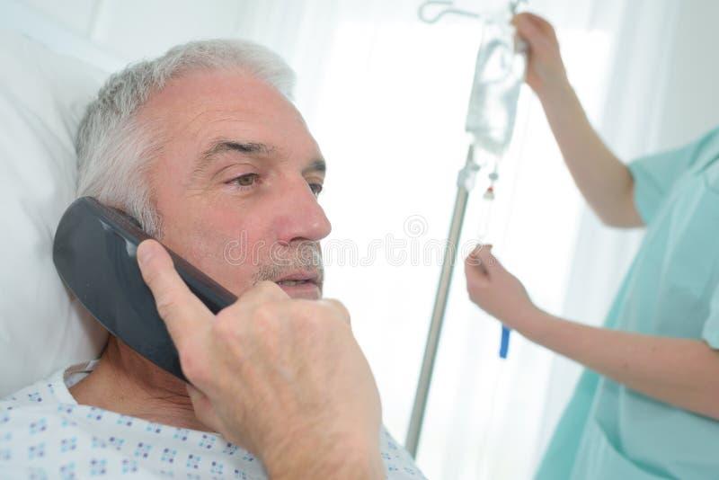 Manlig tålmodig användande mobiltelefon i sjukhussäng royaltyfri bild