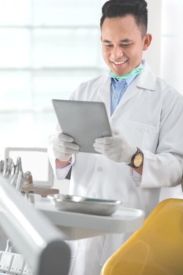 Manlig tandläkare i kliniken genom att använda minnestavlan royaltyfri fotografi