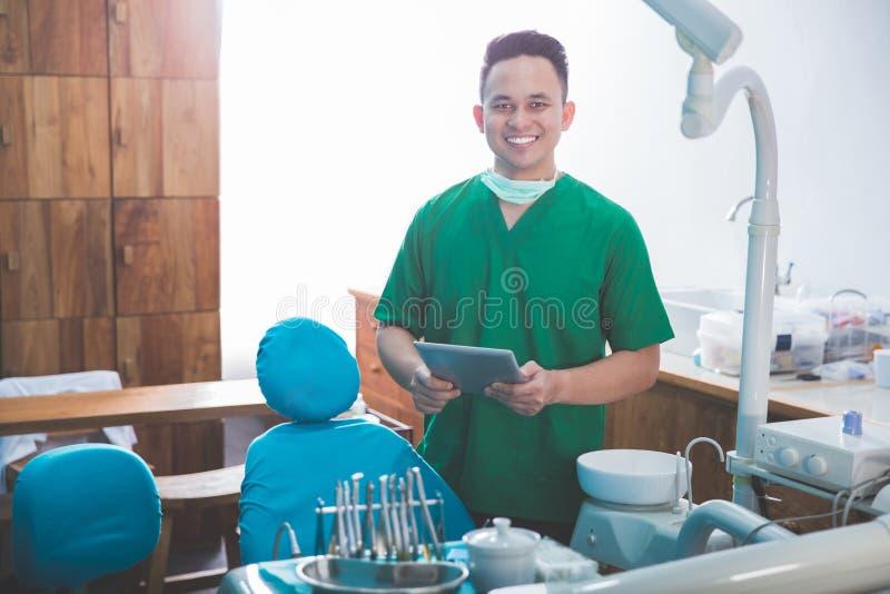 Manlig tandläkare i kliniken genom att använda minnestavlan arkivfoton