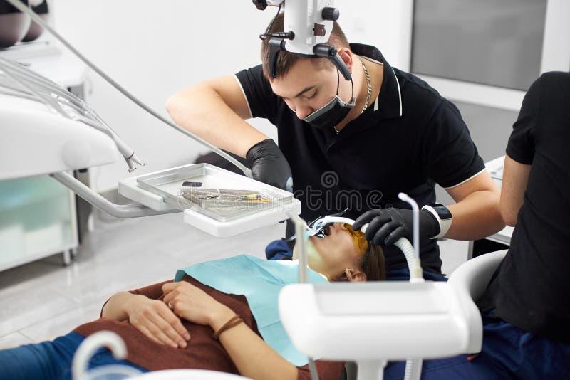 Manlig tandläkare i svarta enhetliga fixandeung flickatänder med tand- instrument royaltyfri fotografi