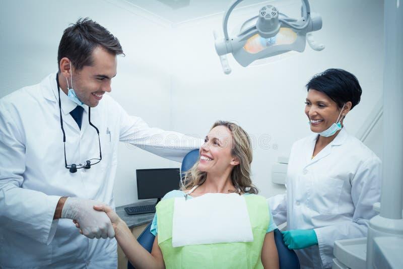 Manlig tandläkare med assistenten som skakar händer med kvinnan arkivfoton