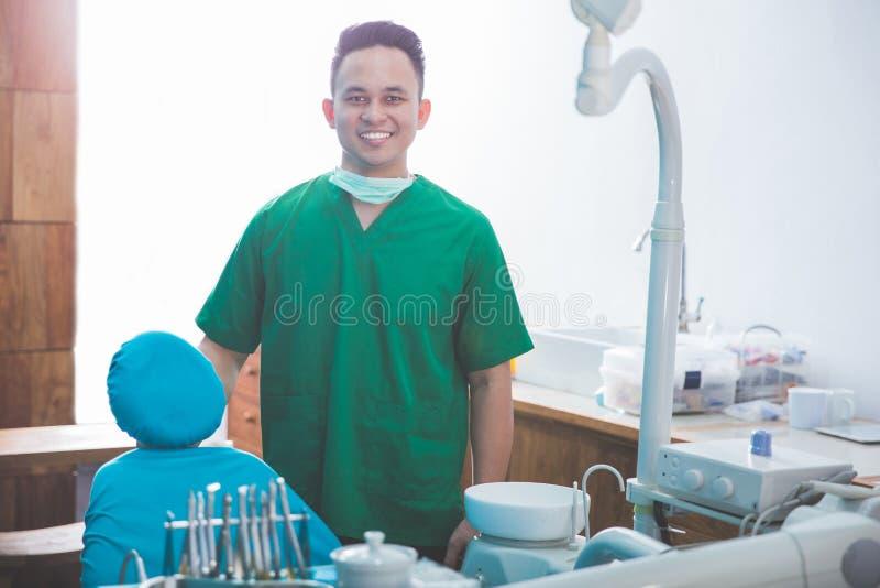 Manlig tandläkare med hjälpmedel över medicinsk kontorsklinik arkivfoton